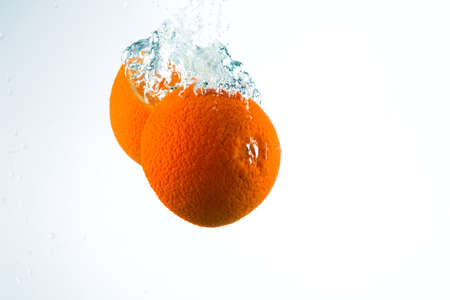 Orange in streams of water on a white background, studio light