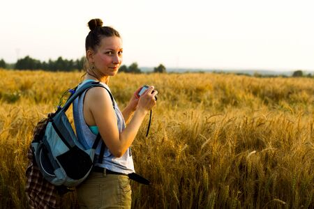 Young girl looks at the sunset on a summer evening at the edge of a rye field