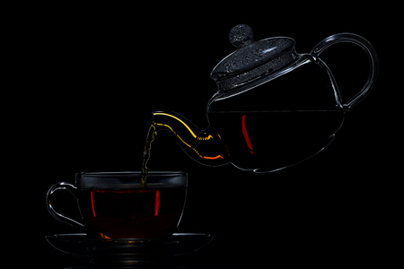 Tea in a transparent teapot on a black background, studio light