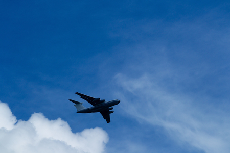 Transport plane flies against the background of a summer blue sky with clouds