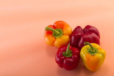Sweet bellpepper. Two red and two yellow-orange sweet bellpeppers on a light pink background. Four pieces. Studio light. Top view