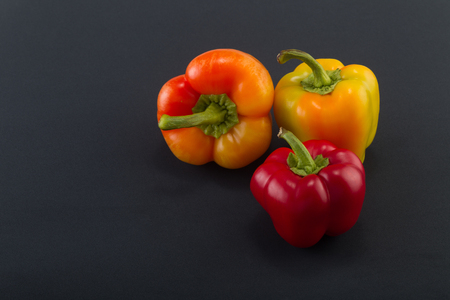 Sweet bellpepper. Two orange-yellow and one red sweet bellpeppers on a black background. Three pieces. Studio light. Top view Stockfoto