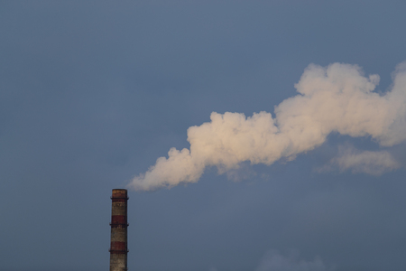 Power industry. Thermal Power Plant. Industrial landscape. Pipes of power station smoke on the background of the cloudy sky Stock Photo