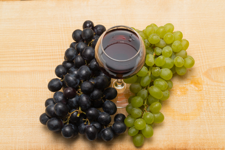 Two clusters of grapes, white and black, and a glass with red wine on a wooden background, studio lighting, top view
