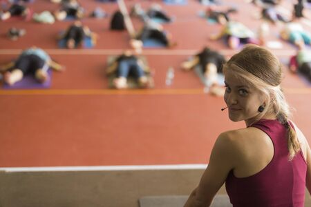 A young girl, a yoga trainer, is engaged with a group of students