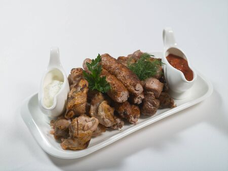 Grilled kebab, chicken and pork skewers, red and white sauce on a plate. Assorted meat. Meat dishes. Banquet, buffet menu