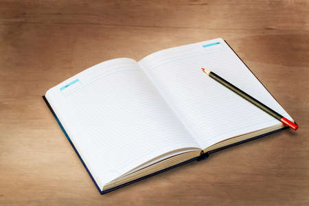 Open diary with a pencil lie on a wooden board, top view