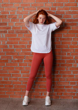 Fashion style studio portrait of beautiful red-haired young girl in leggings pants and white t-shirt. Model standing and posing beside brick wall
