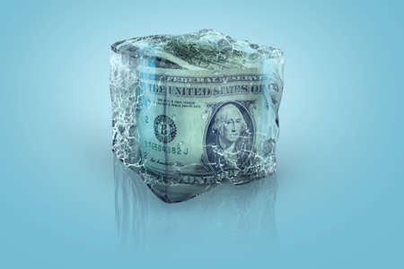 Frozen American money in ice cube on a blue background Stock fotó