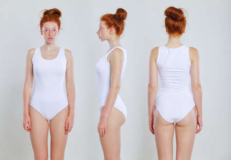 Young caucasian woman model posing in studio in an bodysuit, on gray background. Redhead girl wearing her hair in a bun with healthy freckled skin