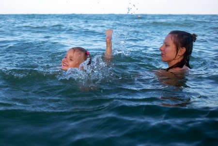 Mother is holding her little daughter. They bathe in the sea, many drops and spray adorable laughing having fun together hot summer day 写真素材