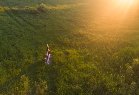 Girl practicing yoga at sunset. Top view. Stock Photo