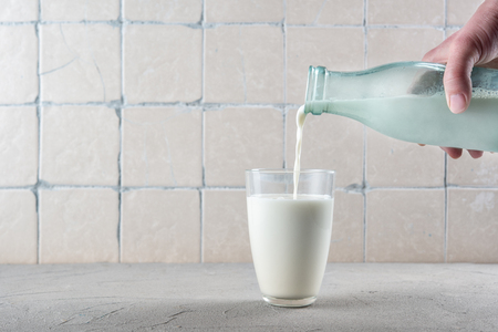 Pouring milk on the kitchen background with ceramic tiles