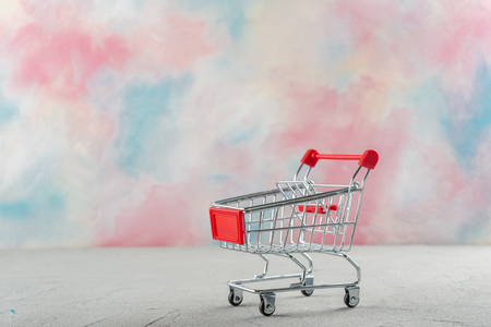 Supermarket trolley on a colored background with a bright color background
