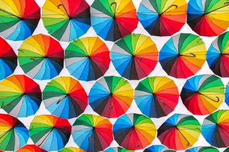 Rainbow colored umbrellas pattern on the street - bottom view Imagens
