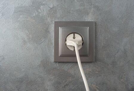 220 volt power plug on a stucco wall background