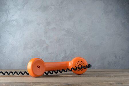 Vintage orange telephone on concrete wall background