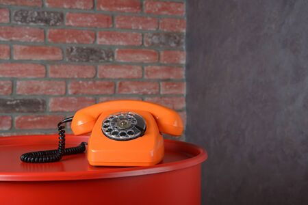 Vintage orange telephone on brick wall background