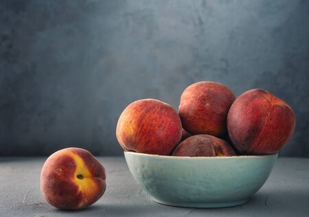 Peaches in a bowl on the table against the wall