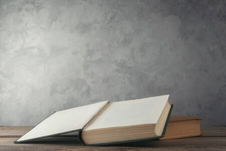Open books on the table against the wall Imagens