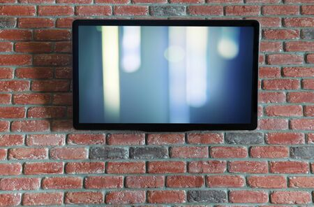 TV on a red brick wall with an abstract splash on the screen