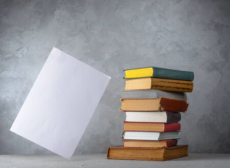 Stack of books on the table and white paper sheet