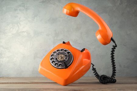 Vintage orange telephone on concrete wall background