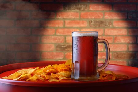Dark beer and chips on a red barrel Imagens