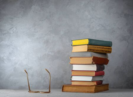 Stack of books on the table and glasses