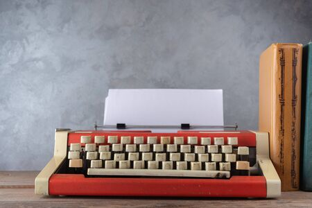 Old red typewriter on the table near the wall Imagens