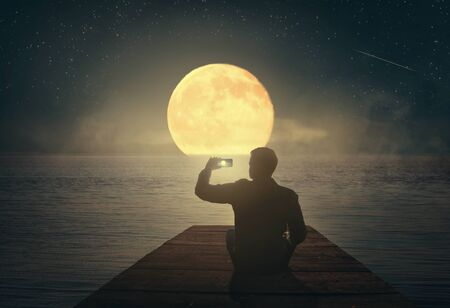 A man sitting on a pier looks at the moon and photographs it on a smartphone Фото со стока