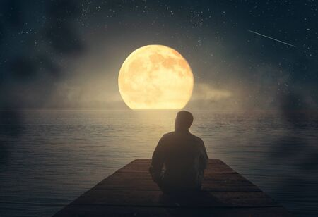 A man sits on the pier and looks at the moon. Standard-Bild