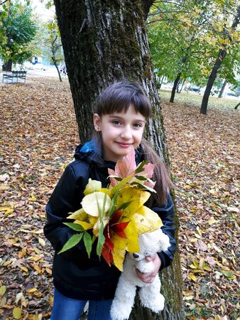 A girl stands near a tree holding in her hand autumn leaves of trees and a teddy bear.