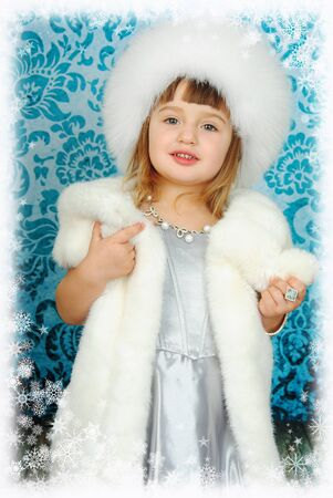 A little beautiful princess with a fluffy white hat on her head holds in her hands a collar from a fur coat, in a frame of snowflakes. New Years holiday concept.