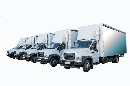 Cinco camioneros blancos en el estacionamiento esperan la próxima entrega de mercancías. El concepto de empresa de transporte para la entrega de mercancías en todo el mundo. Vista lateral. Aislar Foto de archivo
