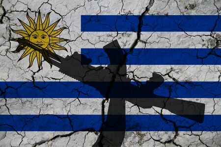 Hand assault rifle on the background  flag of Uruguay and cracks. Uruguay Power Concept.