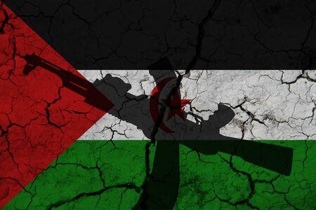 Hand assault rifle on the background  flag of Western Sahara and cracks. Western Sahara Power Concept.