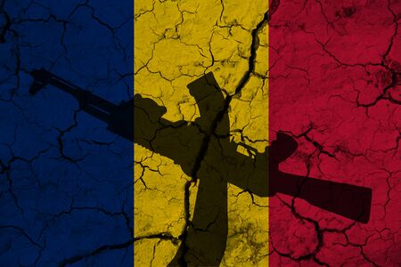 Hand assault rifle on the background  flag of Romania and cracks. Romania Power Concept. Imagens
