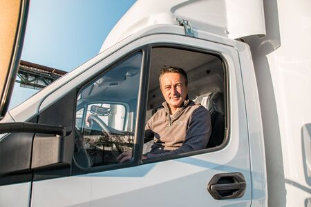 A man driver is sitting in the cab of a modern truck.