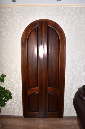 Closed double wooden door in an empty room with copy space.