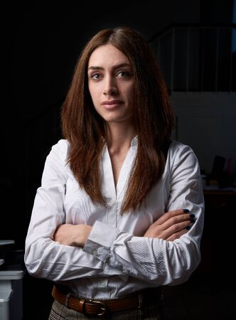 Closeup portrait of a young business woman, happy, cheerful, handsome businessman is standing in a modern office in a white blouse Stock Photo