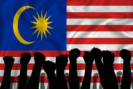 Silhouette of raised arms and clenched fists on the background of the flag of Malaysia. The concept of power, power, conflict. With place for your text.
