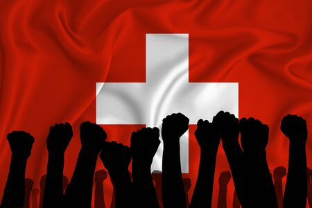 Silhouette of raised arms and clenched fists on the background of the flag of Switzerland. The concept of power, power, conflict. With place for your text.