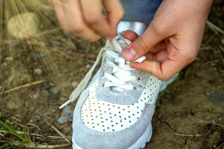 girl ties a lace on white sneakers.