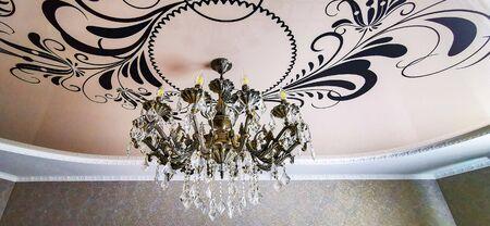 Antique bronze chandelier, bottom view, natural light, ceiling background.
