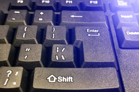 Black and computer keyboard close-up. Overlooking the enter button