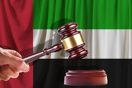 Judge wooden gavel on the background of the flag of United Arab Emirates. Oil and gas industry. The concept of oil fields and oil companies. 스톡 콘텐츠