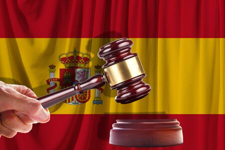 Judge wooden gavel on the background of the flag of Spain. Oil and gas industry. The concept of oil fields and oil companies. Banco de Imagens