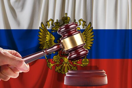 Judge wooden gavel on the background of the flag of Russia. Oil and gas industry. The concept of oil fields and oil companies.