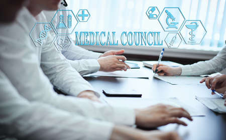 A group of doctors in a modern clinic is planned. The concept of modern medicine and medical biotenology. Medical icons on the screen with the inscription: MEDICAL COUNCIL Stock Photo